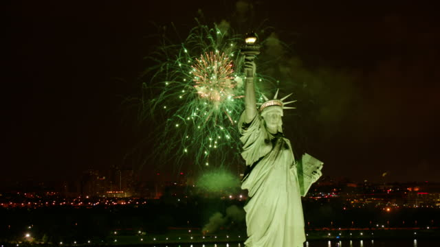 CU ZO AERIAL View of statue of liberty with fireworks and yachts / New York City