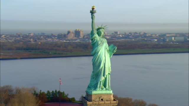 ws pan zo view of statue of liberty with manhattan skyline in background / new york city, new york, usa - statue stock videos & royalty-free footage