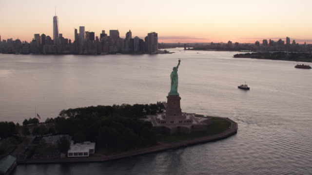 AERIAL MS View of statue of liberty with ships sailing in hudson river and city on a distance at early morning / New York City