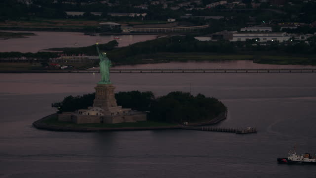 AERIAL MS View of statue of liberty with small houses in city behind at early morning / New York City