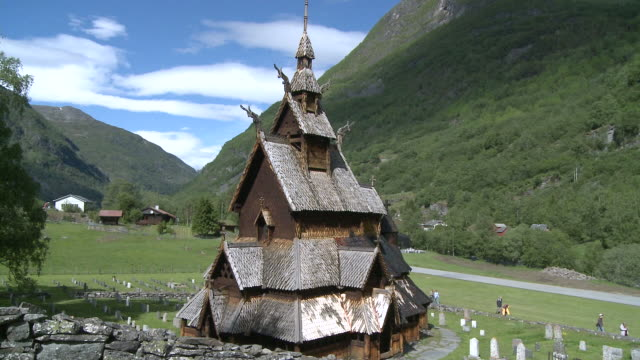 ws view of stave church with people in background / borgund, sogn og fjordane, norway - kirchturmspitze stock-videos und b-roll-filmmaterial