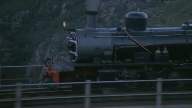 ws aerial ts zo view of steam train moving along tracks - lokomotive stock-videos und b-roll-filmmaterial