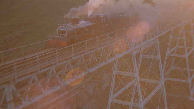 WS AERIAL TS ZO View of Steam train travelling over steel bridge