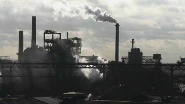 ws view of steel mill with smoke coming out of smoke stacks at dusk / duisburg, north rhine westfalia, germany - ruhr stock videos & royalty-free footage