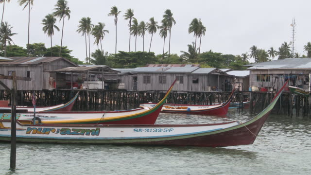 ws view of still villages and longline fishing boats / semporna, sabah, malaysia    - cultura malesiana video stock e b–roll