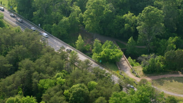 WS ZO AERIAL POV View of Stone Bridge at Bull Run Creek and cars moving on elevated road with forest area / Manassas, Virginia, United States