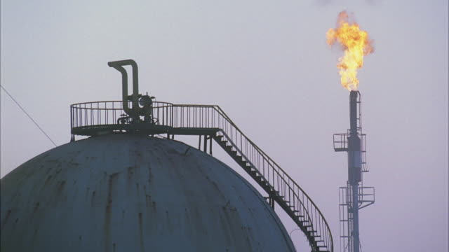 WS View of storage tanks in oil refinery, flame from chimney in background