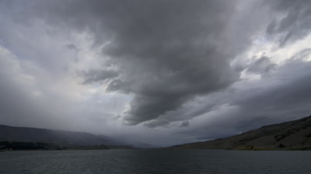 ws t/l view of storm clouds moving over lake at dawn / south island, new zealand - ominous stock videos & royalty-free footage