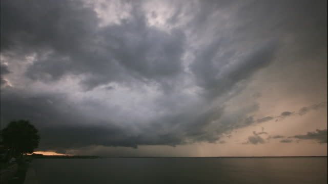 ws t/l view of storm clouds moving rapidly over tampa bay from day to night / tampa, florida, usa - storm cloud stock videos & royalty-free footage