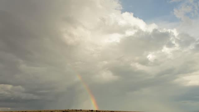 ws td t/l view of storm clouds, rainbow and rain in field / flagstaff, arizona, usa - flagstaff arizona video stock e b–roll