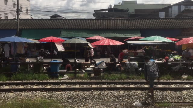 view of street market near na bon train station from the train window - povertà video stock e b–roll