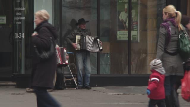 vídeos y material grabado en eventos de stock de ws view of street musicians with pedestrians / riga, latvia - acordeonista