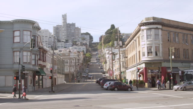 WS View of street on hill with vehicles and buildings / San Francisco, California, United States