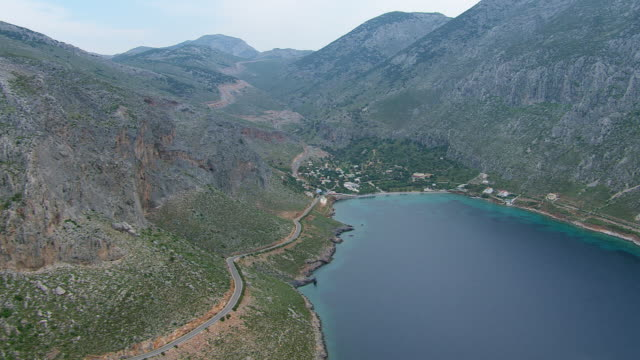 WS AERIAL View of street on mountain and Vathi valley with small town / Kalymnos, Cyclades, Greece