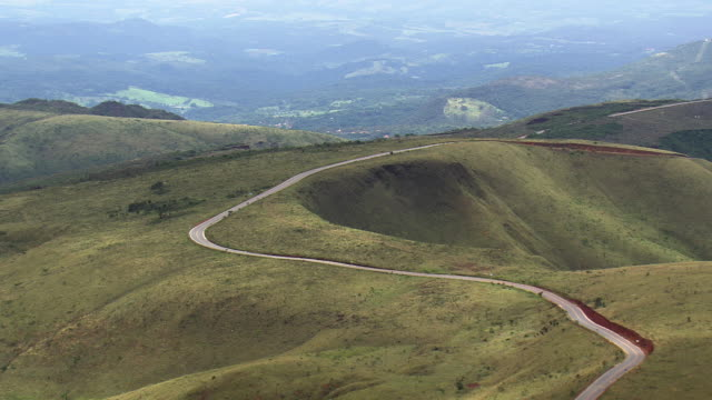 ws aerial view of street over mountain / minas gerais, brazil - minas stock videos and b-roll footage
