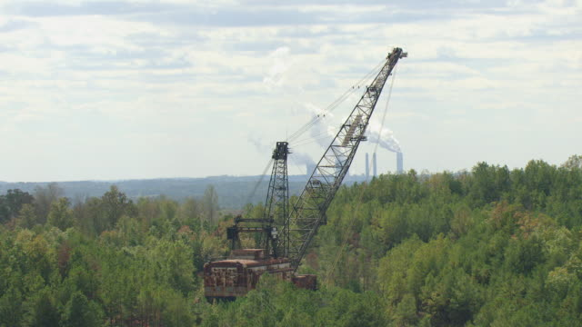 ws aerial view of strip mine crane in field in jefferson county with power plant smoke stacks / alabama, united states - crane construction machinery stock videos & royalty-free footage