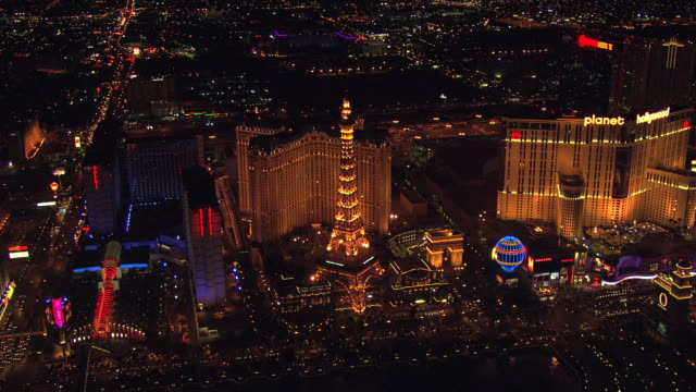 ws aerial zi view of strip with neon lights at night and eiffel tower statue at night / las vegas, nevada, united states - replica eiffel tower stock videos & royalty-free footage