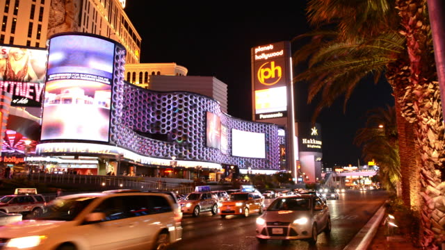 ws view of strip with paris casino at night exposure and traffic moving energy / las vegas, nevada, united states - 商業看板点の映像素材/bロール