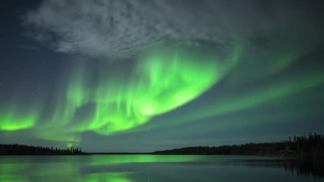 ws t/l view of strong aurora over lake with bit of cloud cover / yellowknife, northwest territories, canada  - serenità video stock e b–roll