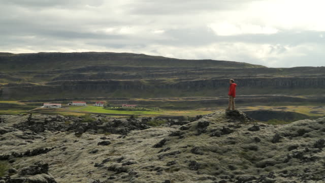 stockvideo's en b-roll-footage met ws view of structures and mountains and man taking picture on mountain cliff / reykjavik, hofudhborgarsvaedhi, iceland  - wiese