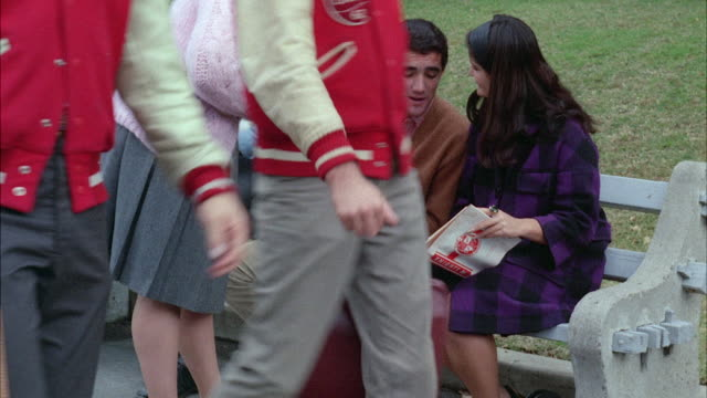 ms view of students on unidentified college campus  - 1960 stock-videos und b-roll-filmmaterial