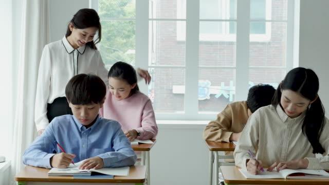 vídeos y material grabado en eventos de stock de view of students studying and teacher supervising a class in elementary school classroom - coreano oriental