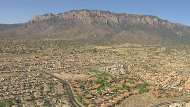 vídeos de stock, filmes e b-roll de ws aerial view of suburbs with mountains / albuquerque, new mexico, united states - novo méxico