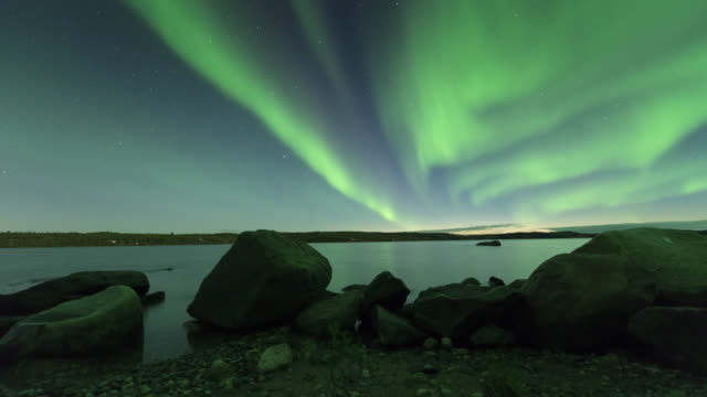 vídeos de stock, filmes e b-roll de ws t/l view of summer aurora with rocks in foreground and reflection on calm lake / yellowknife, northwest territories, canada  - 1 minuto ou mais