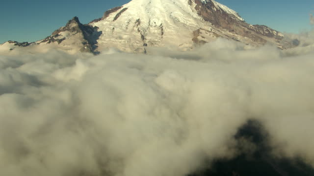 ws aerial tu view of summit of mount rainier surrounded by clouds / washington, united states - mt rainier stock videos & royalty-free footage