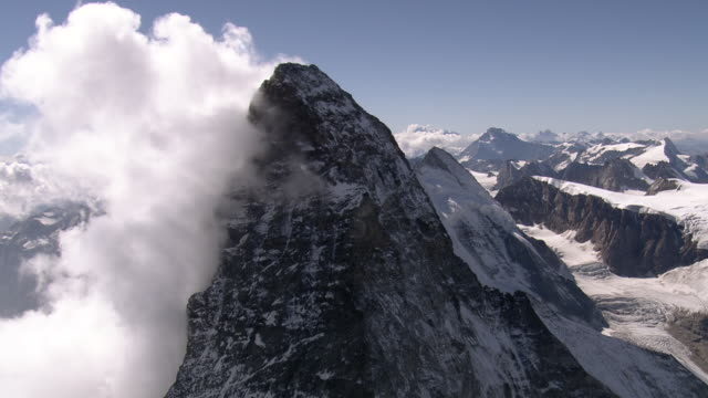 ws aerial view of summit ridge and three mountaineers on italian summit with fog zone on south side / matterhorn, valais, switzerland - mountain peak stock videos & royalty-free footage