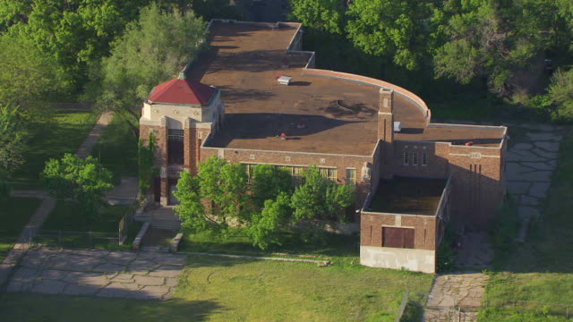 ms aerial view of sumner elementary school surrounded by tree / topeka, kansas, united states - 小学校点の映像素材/bロール