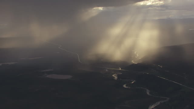 WS AERIAL View of sun peaking out of stormy clouds north of Chugach Mountains / Alaska, United States