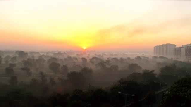 WS View of Sun rises over foggy landscape / Delhi, India