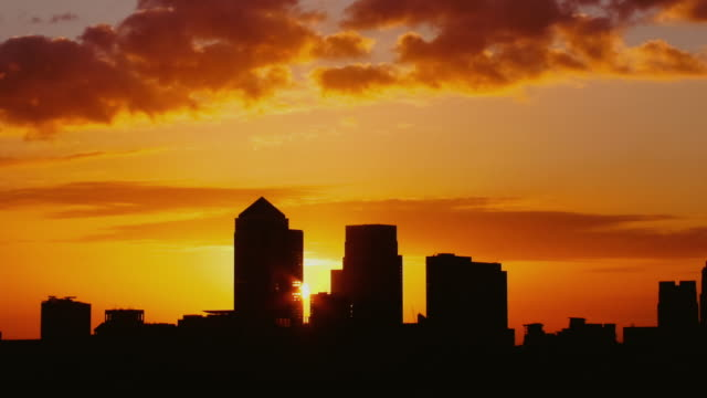MS T/L PAN View of Sun rising behind Canary Wharf city / London, United Kingdom