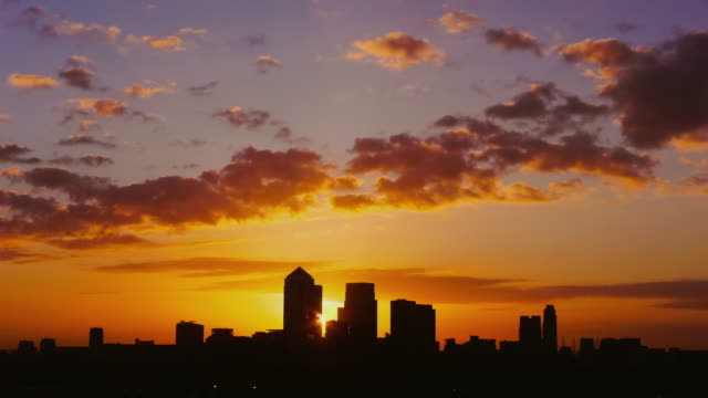ws t/l pan view of sun rising behind canary wharf city / london, united kingdom - sunrise dawn stock-videos und b-roll-filmmaterial