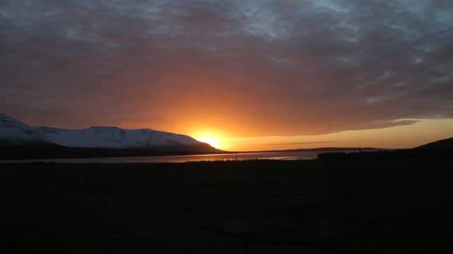 ws view of sun sets in distance behind oceanside cliff with water / skagafjorour, nordhurland vestra, iceland  - wiese stock videos & royalty-free footage