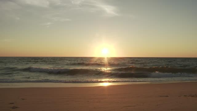 vidéos et rushes de ws t/l view of sun setting into atlantic ocean in france / cap de l'homy, aquitaine, france - aquitaine