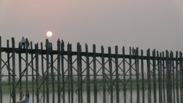 ws t/l view of sun setting on bridge / mandalay, mandalay division, myanmar - mandalay stock videos and b-roll footage