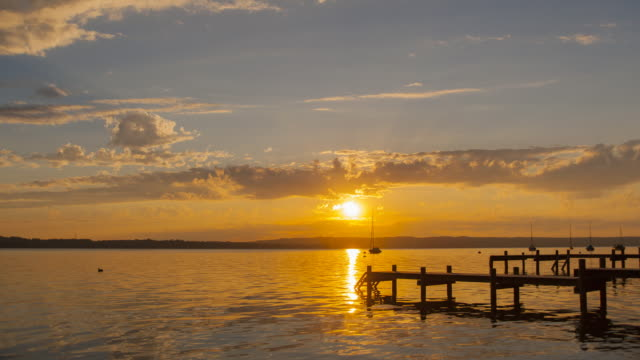 WS T/L View of sun setting over lake 'Starnberger See' from day to night / Ambach, Bavaria, Germany