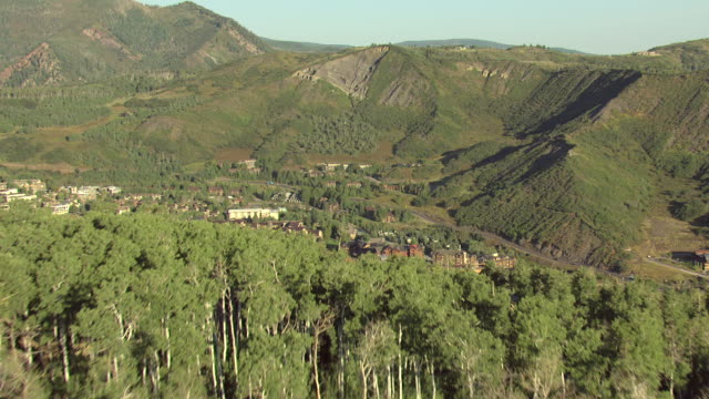 WS AERIAL View of sun shining on aspen tree forest on mountain top, snowmass winter resort village in valley with surrounding mountains / Aspen, Colorado, United States