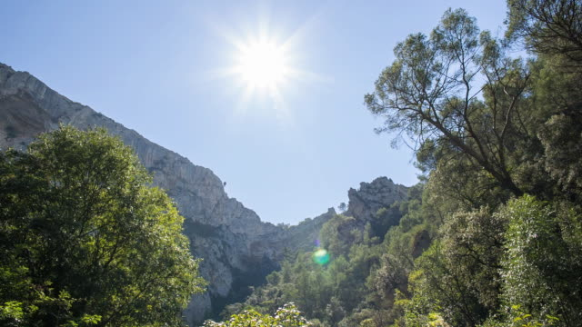 WS View of Sun shining over mountain with trees / Fontaine de Vaucluse, Vaucluse, France
