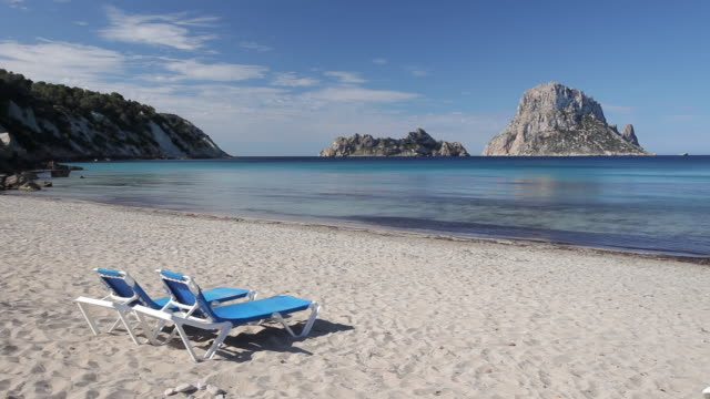 WS View of Sunbeds on beach Cala Carbo Bay and Es Vedra Island / Ibiza, Balearic Islands, Spain