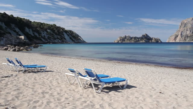 WS PAN View of Sunbeds on beach Cala Carbo Bay and Es Vedra Island / Ibiza, Balearic Islands, Spain