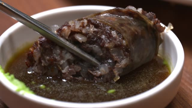 view of sundae(type of blood sausage in korea) being dipped into soy sauce with wasabi - wasabi sauce stock videos and b-roll footage