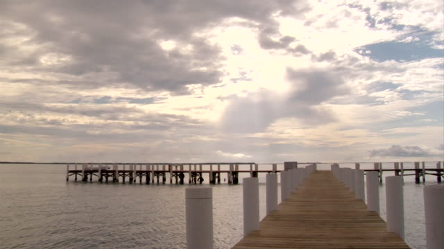 ws view of sunlight breaks through clouds with jetty / abergris caye, belize, belize - wiese stock videos & royalty-free footage
