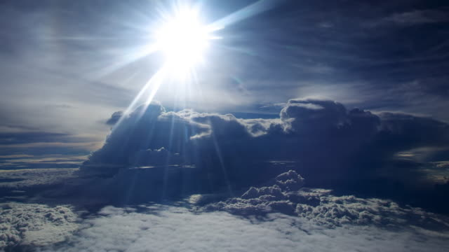 ws aerial t/l view of sunlight flares over spacey blue cloud formations with little disc like cloudlets / in flight, indonesia - aircraft point of view stock videos & royalty-free footage