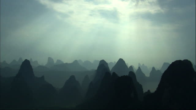 View of sunlight shining down on the silhouette of Guilin hills, southern China