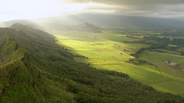 ws aerial view of sunrays beaming upon green landscape of napali coast below on island of kauai / hawaii, united states - na pali coast state park stock videos & royalty-free footage