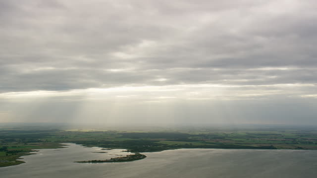 ws aerial zi view of sunrays passing through clouds wit landscape and coastline at greifswald / germany - küste stock-videos und b-roll-filmmaterial