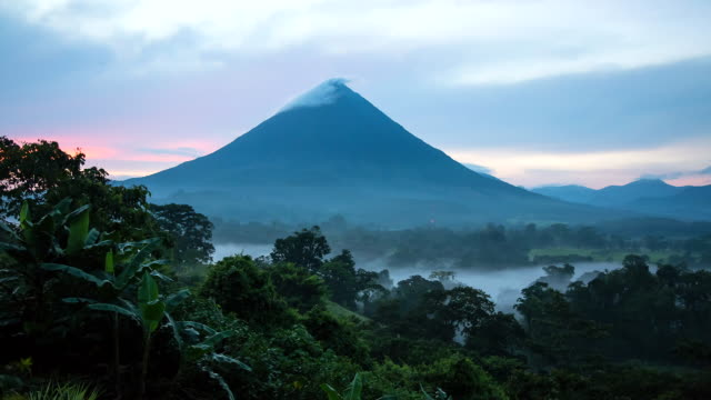 ws t/l view of sunrise on arenal volcano and jungle with clouds moving over / la fortuna, alajuela, costa rica - costa rica video stock e b–roll